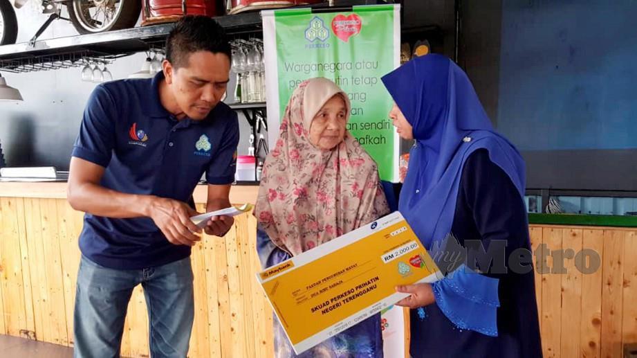 CHE Farihah (kanan) bersama Pegawai Perhubungan PERKESO Mohd Sabri Ramli (kiri) menyampaikan Faedah Pengurusan Jenazah kepada Rabiah. FOTO Zaid Salim