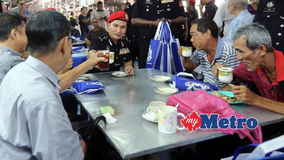 WAN Abdullah (duduk, tiga kanan) minum pagi serta beramah mesra dengan penduduk ketika Program Community Policing. FOTO Danial Saad