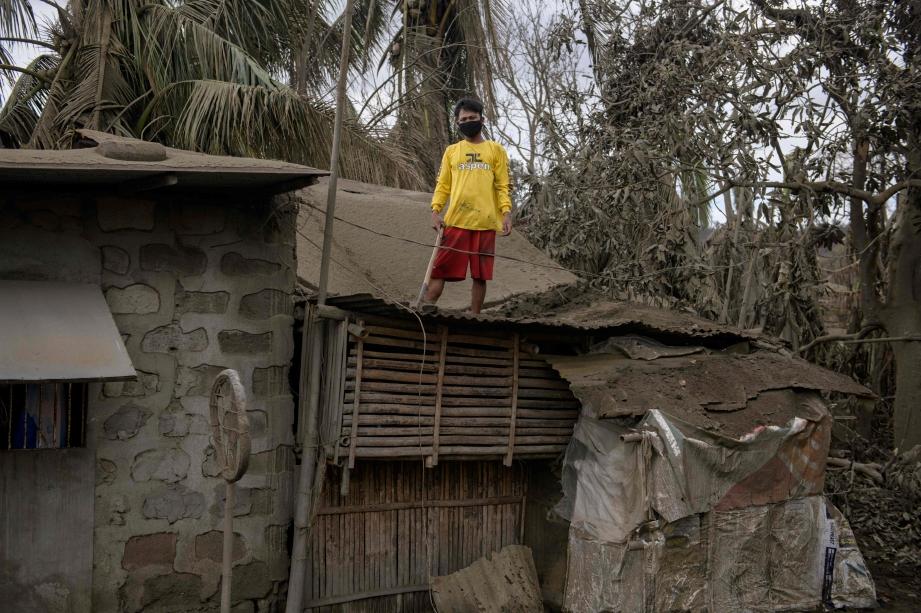 HENRY Pardo sedang membersihkan abu gunung berapi yang diletupkan selepas letusan gunung berapi Taal, dari bumbung rumahnya berhampiran Agoncillo. FOTO AFP