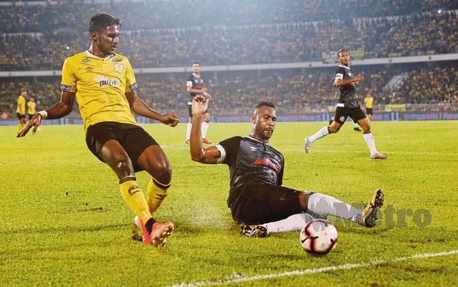 PEMAIN  Perak,  J Partiban  (kiri) mengasak pemain Pahang, Herold  Goulon  di Stadium Perak. - FOTO  Abdullah Yusof