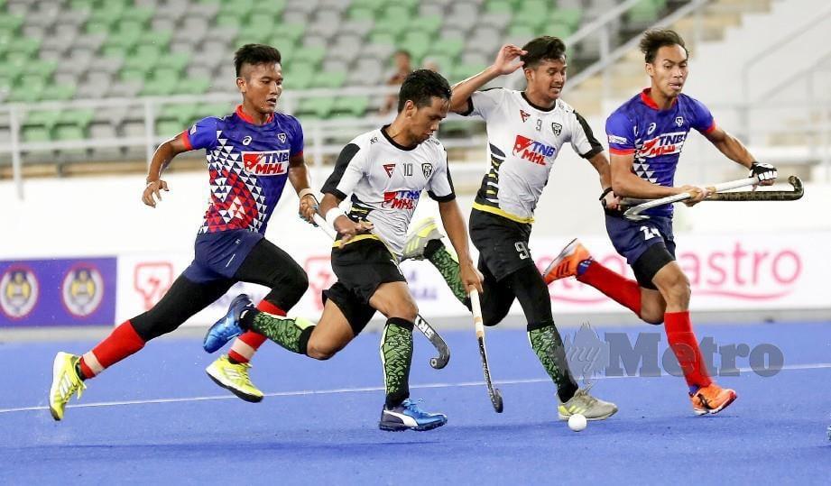 FAIZAL (dua kiri) cuba melepasi kawalan pemain TNB dalam aksi separuh akhir lelaki Piala TNB di Stadium Hoki Nasional Bukit Jalil, baru-baru ini. FOTO Owee Ah Chun