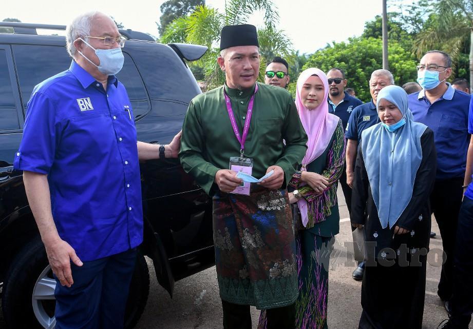 MOHD Sharim Md Zain (dua kiri) bersama isteri, Norhiliyana Abd Hamid (tiga kiri) diiringi Ahli Parlimen Pekan, Datuk Seri Najib Razak untuk mengundi pada PRK DUN Chini di KAFA Felda Chini 3 hari ini. FOTO Bernama