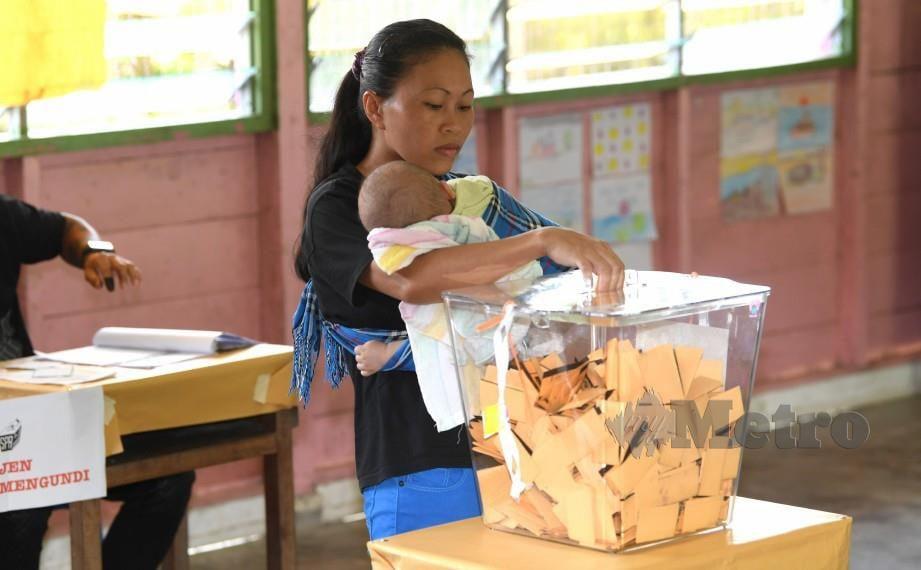 PENGUNDI Rusni Jaison, 30, memasukkan kertas undi sambil mendukung anaknya di Sekolah Rendah Jenis Kebangsaan (C) Cheng Ming. FOTO Bernama