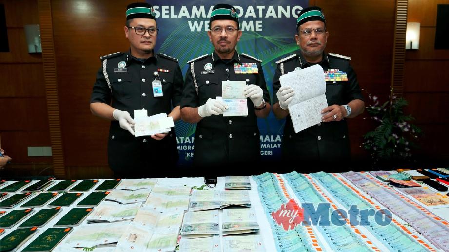 MUSTAFAR (tengah) menunjukkan passport yang dirampas berhubung kes penyeludupan manusia. Turut bersama, Timbalan Ketua Pengarah Operasi Imigresen, Datuk Jaafar Mohamed (kanan) dan Timbalan Pengarah Bahagian Operasi, Siasatan & Pendakwaan JIM, Eadie Nor Faizal Othman (kiri). FOTO Ahmad Irham Mohd Noor