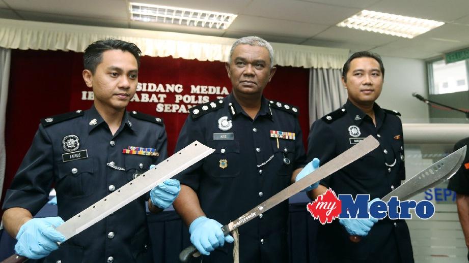 ABDUL Aziz diapit oleh Ketua Jabatan Siasatan Jenayah IPD Speang, Deputi Superintendan Fairus Jaafar (kiri) dan Pegawai Penyiasat, Inspektor Harizan Misron (kanan) menunjukkan senjata yang dirampas daripada suspek. FOTO Mohd Fadli Hamzah