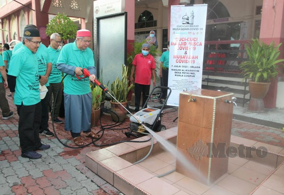 Dr. Zulkifli (kanan) melakukan gimik pelancaran Program Cuci-Cuci Masjid di Masjid Al-Khasyi'in, Desa Petaling anjuran Yayasan Dakwah Islamiah Malaysia (YADIM) bersama Jabatan Perdana Menteri (JPM). FOTO MUSTAFFA KAMAL