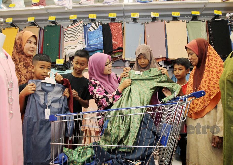 Rosmiza (empat kiri) bersama dengan sebahagian keluarga yang menerima bantuan baju raya dalam Program Kongsi Raya, di pasar raya Mydin. FOTO Nik Abdullah Nik Omar