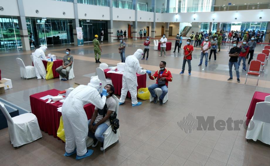 PETUGAS kesihatan menjalankan saringan Covid-19 ke atas pekerja binaan warga asing di Kuala Lumpur, baru-baru ini. FOTO ROHANIS SHUKRI.