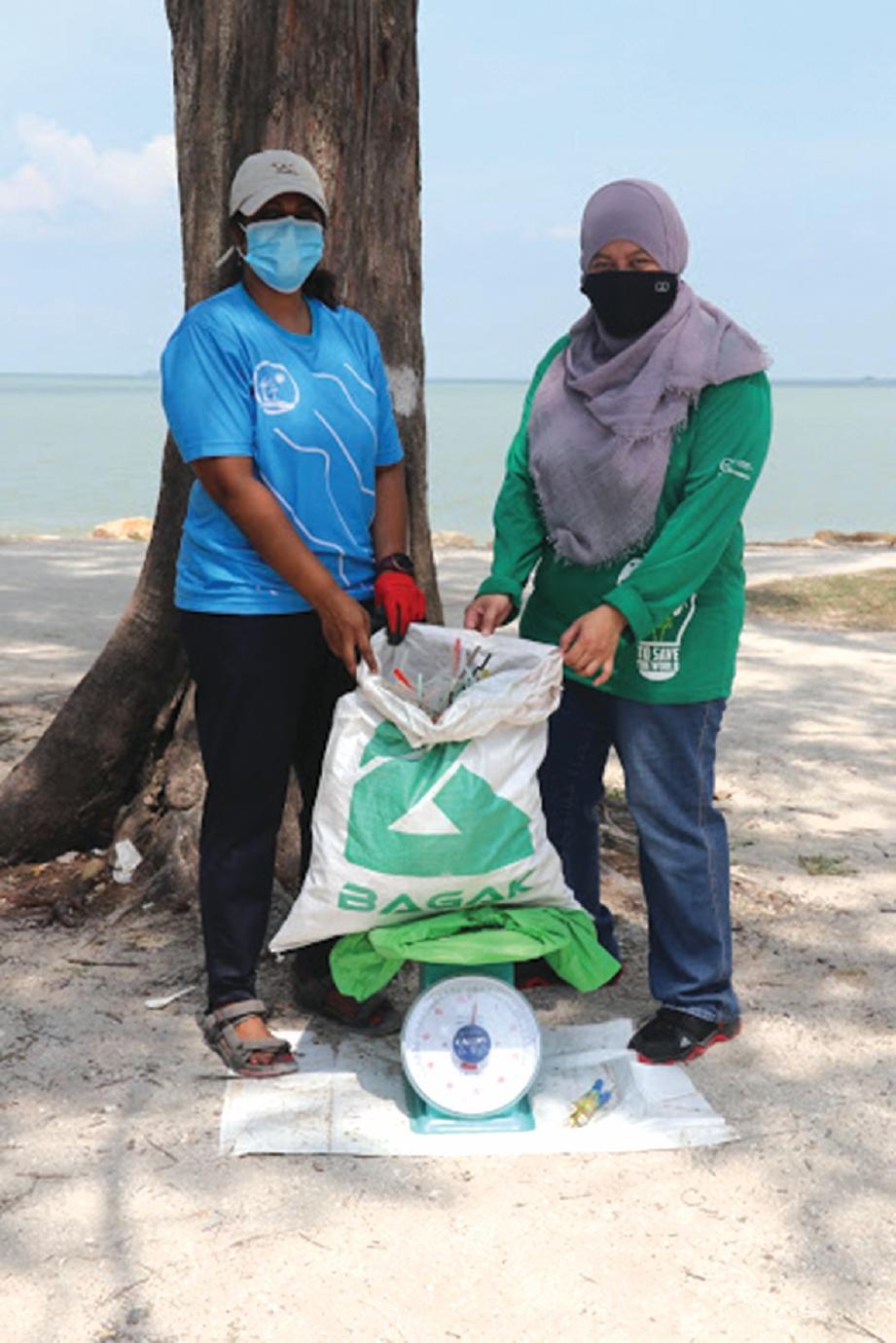 FARAHIYAH ( kanan) turut menyertai aktiviti amal membersihkan kawasan Pantai Remis.