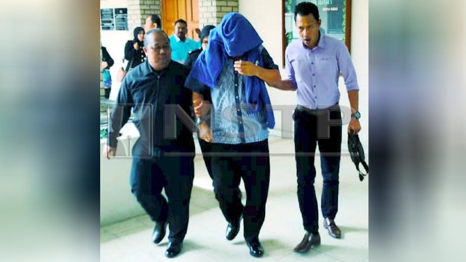 PEGAWAI SPRM membawa Kasrin keluar dari Mahkamah Sesyen Sandakan selepas mengaku tidak bersalah atas pertuduhan mendapatkan suapan. FOTO Poliana Ronnie Sidom