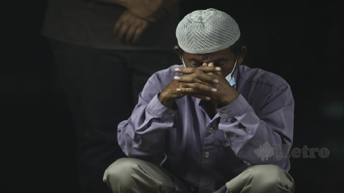Ismail menahan kesedihan ketika pengebumian anaknya. FOTO Ghazali Kori