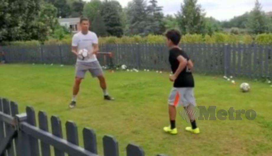 Ronaldo (kiri) melakukan latihan bersama anak lelakinya. FOTO Agensi