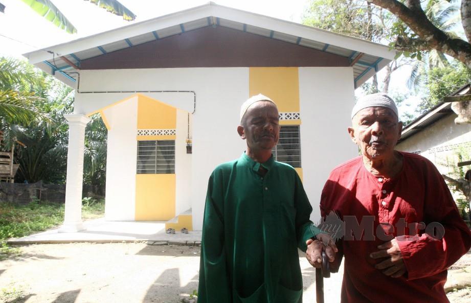 HARUN Isa, 75, bersama anaknya yang OKU cacat penglihatan sejak lahir, Mohd Nazir Harun, 46, di hadapan rumah mereka, hari ini. FOTO Zaman Huri Isa.