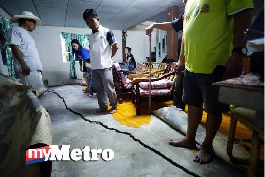 JOSEPH Ebin, 40 (kiri), meneliti rekahan pada lantai rumahnya di Kampung Kiau Toburi, Kota Belud akibat gempa bumi di Ranau. FOTO Lano Lan