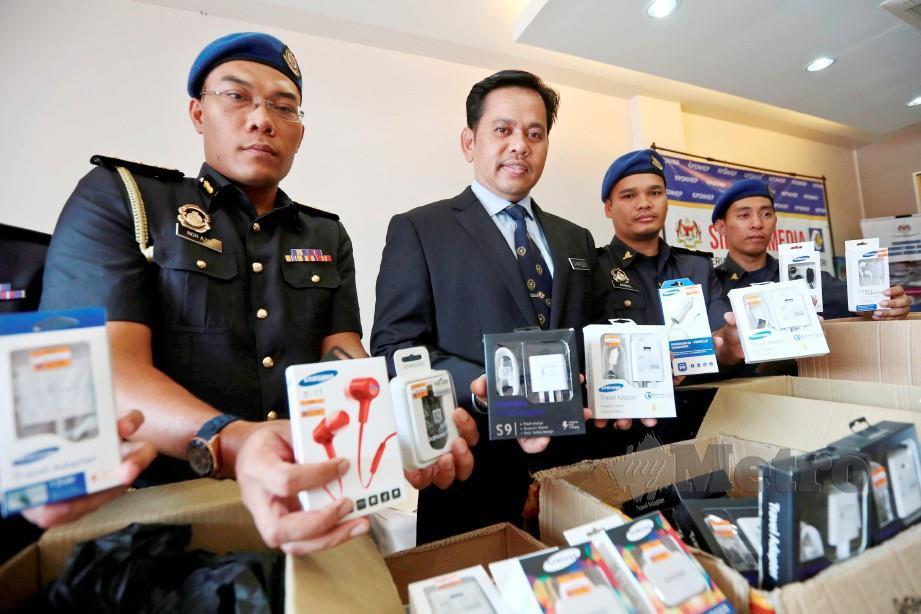 SAHARUDDIN (dua kiri) menunjukkan hasil rampasan barangan jenama Samsung dianggarkan bernilai RM75,299 selepas menahan dua suspek di Kuala Terengganu. FOTO Ghazali Kori