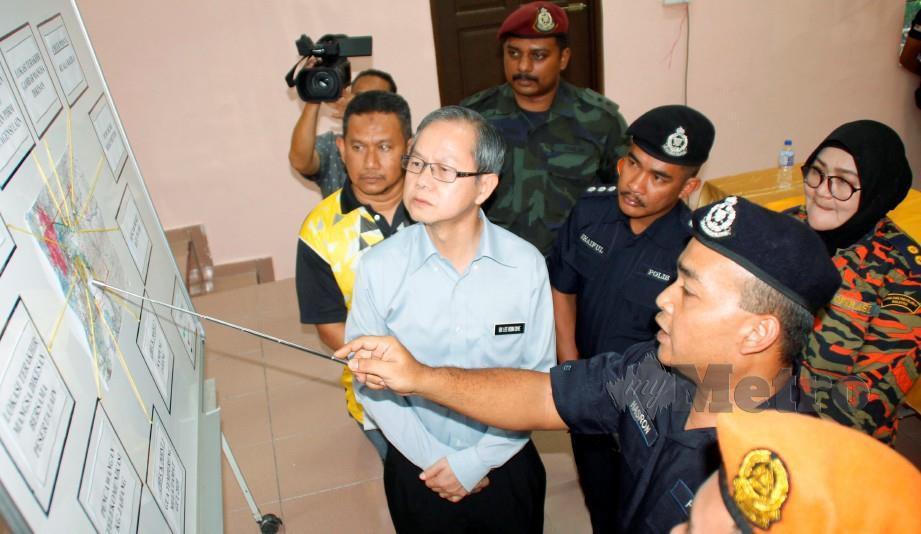 HASRON Nazri ketika memberi penerangan operasi kepada Dr Lee (dua kiri) di Dewan Orang Ramai Kampung Pintu Padang. FOTO Balqis Jazimah Zahari.