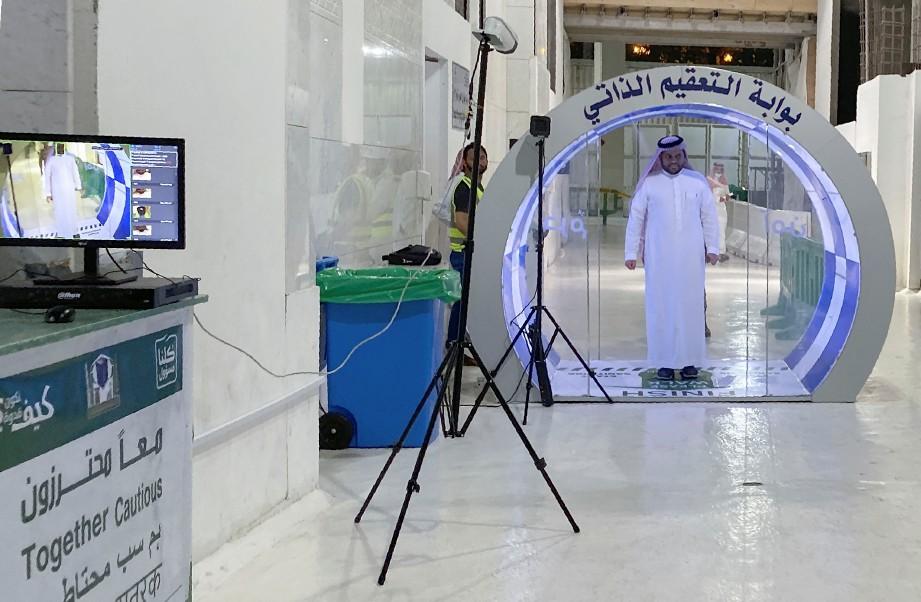 LELAKI memasuki mesin penyah kuman sebelum memasuki Masjidilharam di Makkah. FOTO AFP
