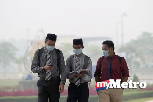 PELAJAR Fakulti Pengajian Bahasa Utama (dari kanan) Muhammad Thaqif Abraqi, 19; Nik Ahmad Hafiz Nik Ahmad Suffian, 20; dan Muhammad Shauqi Hadi, 19, berjalan menuju ke fakulti pengajian dengan menggunakan topeng muka berikutan keadaan jerebu di Universiti Sains Islam Malaysia (USIM), Nilai. FOTO Iqmal Haqim Rosman