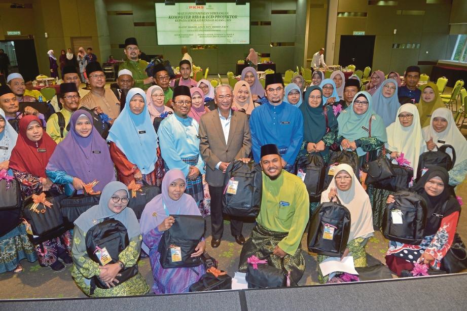 WAKIL SRA bersama Mohd Azizi (tengah) selepas menerima sumbangan komputer riba dan projektor LCD. FOTO Faiz Anuar