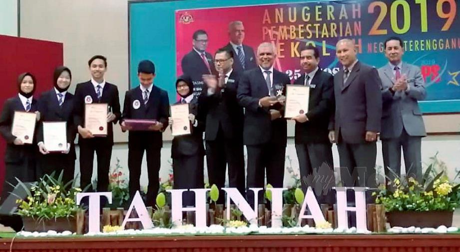 MOHD Zaki (tiga dari kanan) menerima sijil penghargaan daripada Shafruddin sambil diperhatikan lima pelajar Murid Bestari Cemerlang Ikon Kejuruteraan Reka Bentuk. FOTO Malik Muhamad.