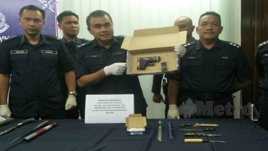 WARI (tengah) menunjukkan senjata yang dirampas selepas menahan seorang lelaki di KM3, Jalan Kuala Perlis-Changlun. FOTO Dziyaul Afnan Abdul Rahman.