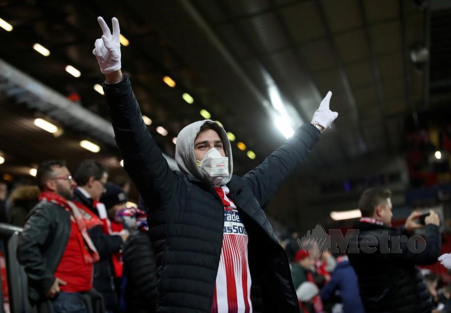 Penyokong memakai topeng muka ketika menyaksikan perlawanan bola sepak. FOTO Reuters