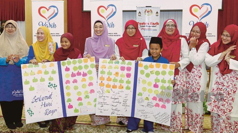 SHAMSHIDA  (empat dari kiri) menerima dua kad raya khas kepada KASIH Malaysia) yang disampaikan wakil anak yatim pada majlis menyampaikan sumbangan duit raya dan Kit Kasih di Masjid Tuanku Mizan Zainal Abidin, Putrajaya, hari ini. FOTO Ahmad Irham  Mohd Noor.