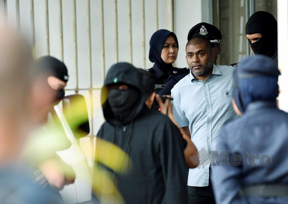 Chandru (dua dari kanan) diiringi anggota polis keluar dari Mahkamah Sesyen Ayer Keroh, Melaka hari ini. Rasul Azli Samad