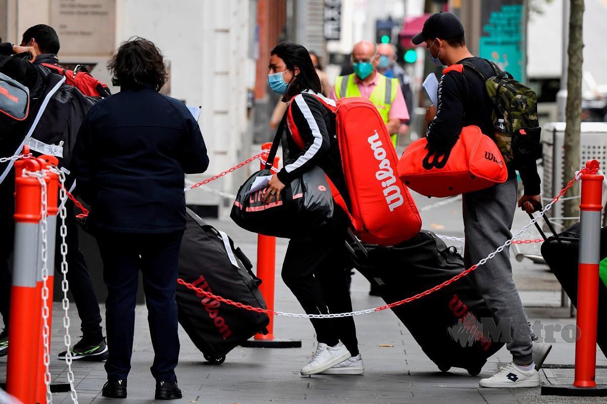 BARISAN pemain dan jurulatih tiba di hotel di Melbourne sebelum perlu menjalani kuarantin selama dua minggu menjelang saingan Terbuka Australia. FOTO AFP