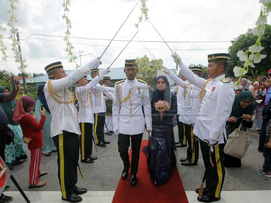Muhd Fuad Hazim bersama pasangannya Siti Shahira diberi penghormatan pegawai dari Kem Mahkota Kluang ketika majlis persandingan mereka. FOTO Adnan Ibrahim