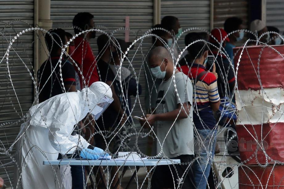 PETUGAS Jabatan Kesihatan Daerah Lembah Pantai memantau penghuni flat Malayan Mansion untuk mengambil sampel berikutan penemuan kes Covid-19 ketika perlaksanaan Perintah Kawalan Pergerakan Diperketatkan (PKPD) di Masjid India, Kuala Lumpur. FOTO Aizuddin Saad