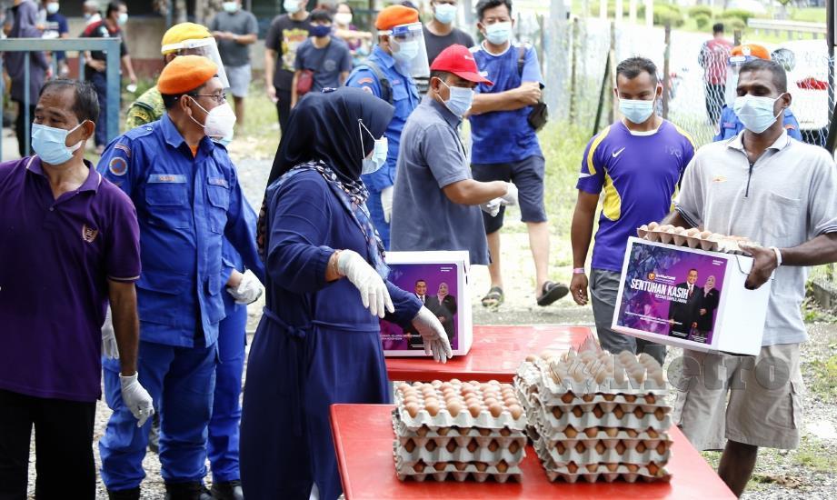 ORANG ramai yang terbabit dalam proses saringan COVID-19 mengambil sumbangan daripada Pejabat ADUN Bukit Kayu Hitam di Dewan Orang Ramai Napoh. FOTO AMRAN HAMID