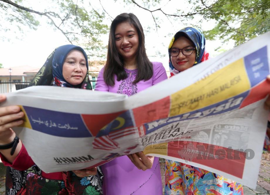 PENASIHAT Kewangan, Chan Chya Zhuo, 24, (tengah) bersama rakannya, Nur Shamshazana Mohd Zahir, 22, (kanan) dan Noriah Madon Mashaid, 46, teruja  membaca Harian Metro berwajah baharu. FOTO Sharul Hafiz Zam