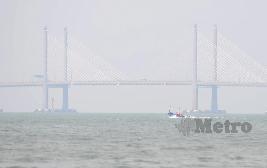 Jambatan Sultan Abdul Halim Muadzam Shah hampir tidak kelihatan kerana jerebu ketika dirakamkan di Bayan Lepas. Foto Shahnaz Fazlie Shahrizal