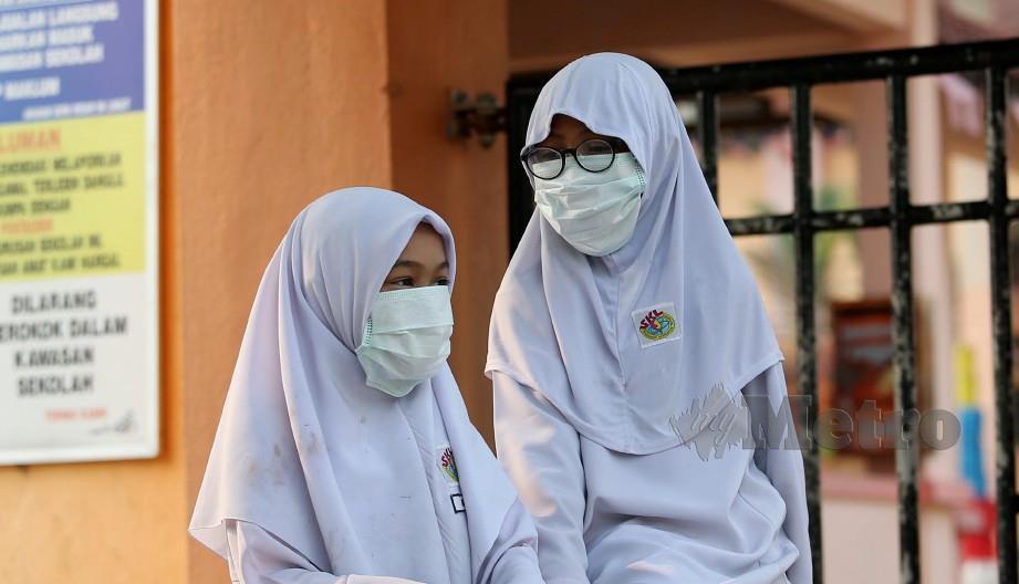 MURID sekolah mengenakan penutup hidung dan mulut berikutan jerebu melanda di seluruh negara. FOTO IQMAL HAQIM ROSMAN