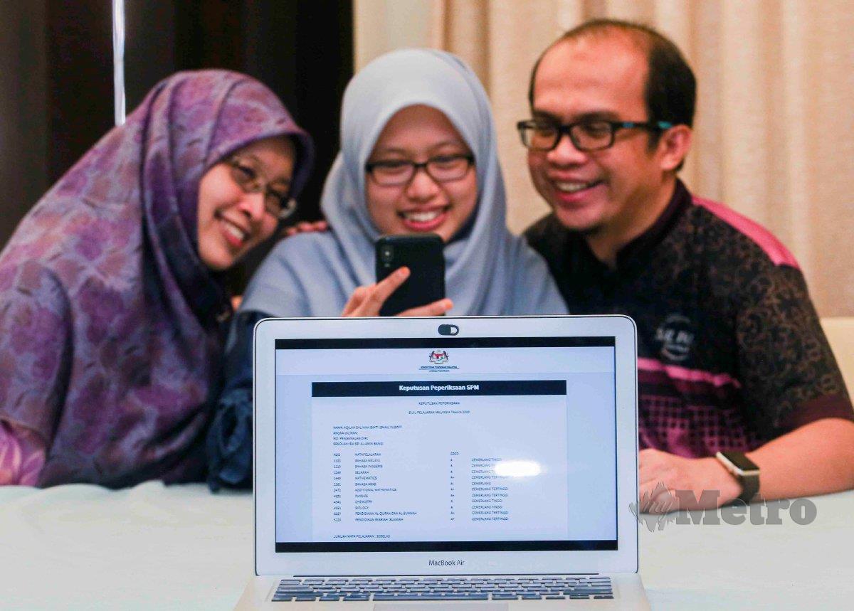 AQILAH Salihah  (tengah) berkongsi kegembiraan bersama ibu bapanya selepas memperoleh keputusan  11A dalam SPM ketika tinjauan di Presint 15, Putrajaya, semalam.