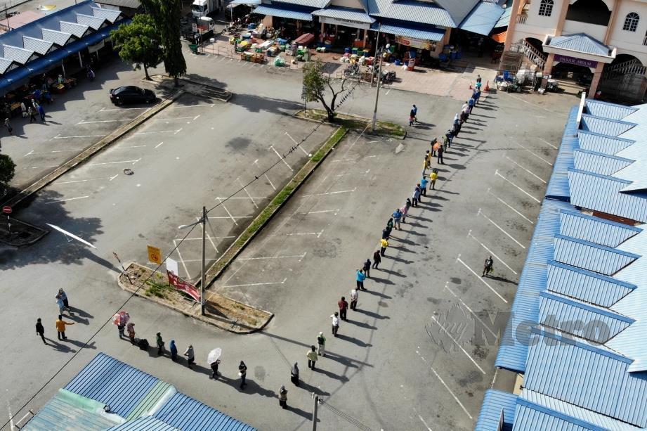PENGUNJUNG beratur panjang mematuhi penjarakan sosial untuk membeli barang keperluan di Pasar Awam Batu Gajah. FOTO Sharul Hafiz Zam