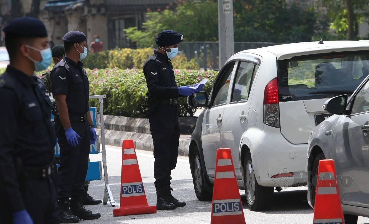 Anggota Polis dibantu anggota ATM memeriksa kenderaan yang melalui sekatan jalan raya (SJR) di Jalan Sultan Azlan Shah. FOTO NSTP