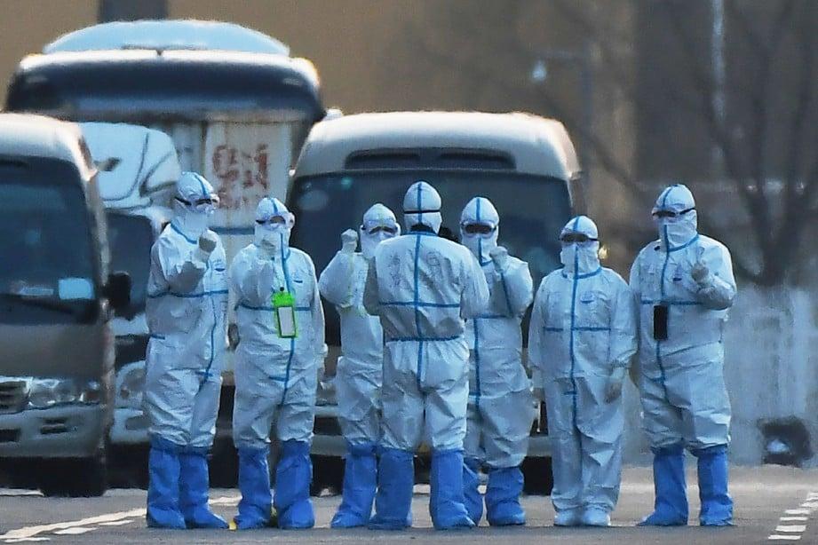 KAKITANGAN memakai sut keselamatan ketika melakukan saringan kesihatan kepada semua individu yang memasuki Beijing. FOTO AFP