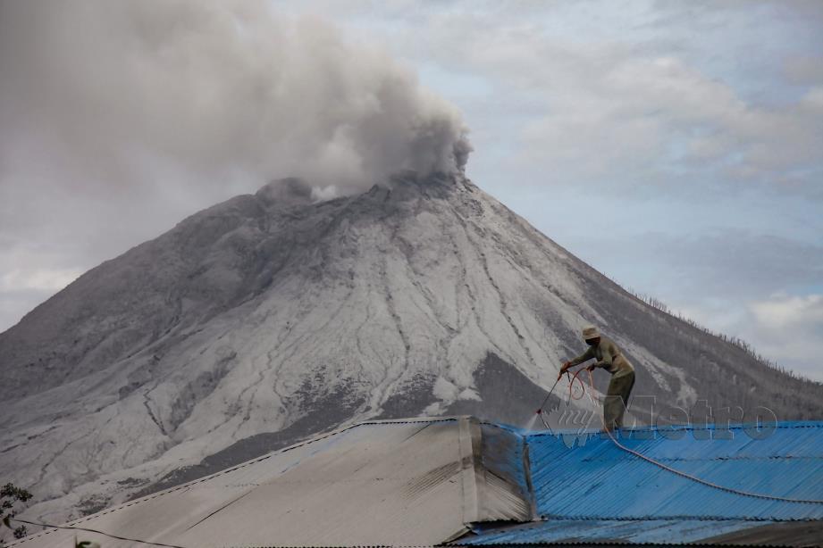 PENDUDUK di Kampung Naman Teran di Karo, Sumatera Utara, membersihkan kediamannya yang terjejas akibat letusan Gunung Sinabung, kelmarin. FOTO AFP