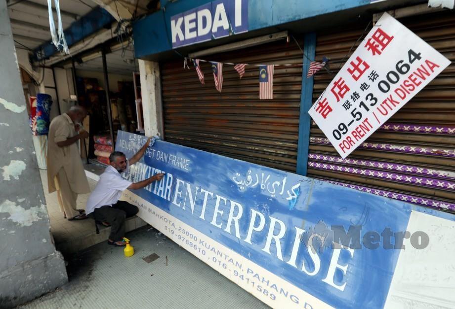 PEKERJA premis perniagaan menukar papan tanda dari tulisan rumi ke Jawi di bandar Kuantan. FOTO arkib NSTP