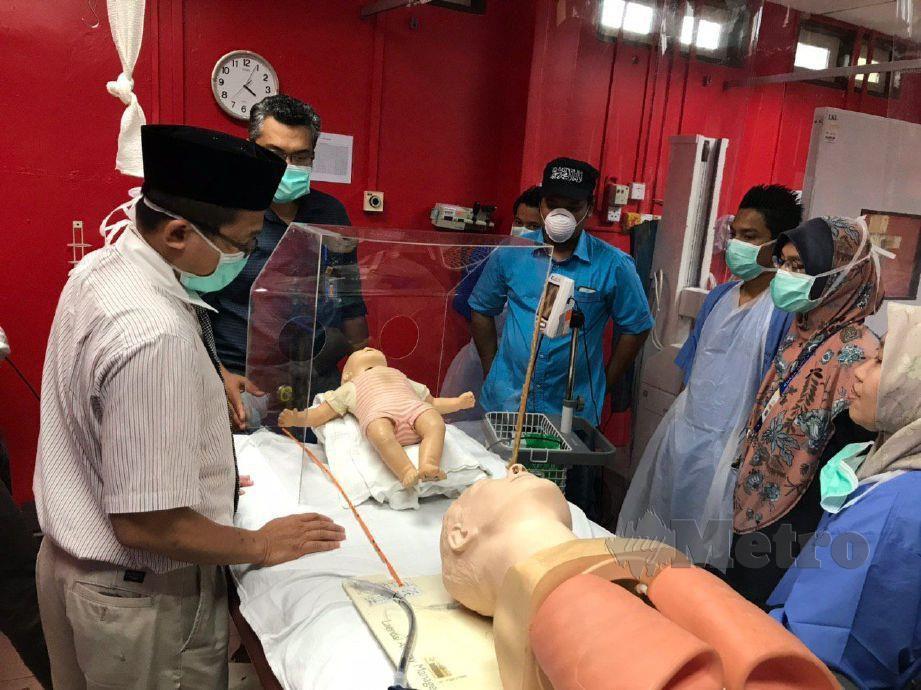 PENSYARAH UC TATI, Amirul Hakim Embong (tengah) sedang memberi penerangan mengenai 'Sterilization Chamber' kepada kakitangan Hospital Kemaman. FOTO IHSAN UC TATI