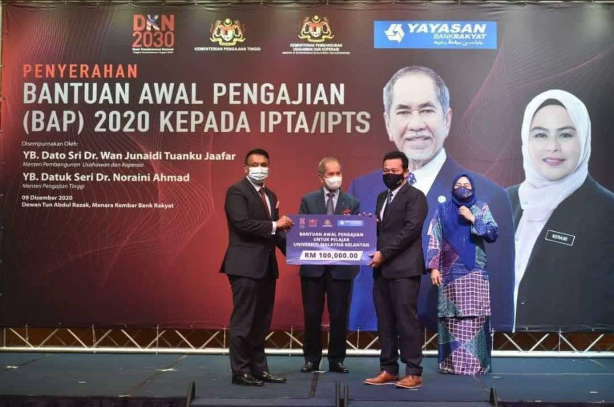 DR NOOR Azizi (dua dari kanan)  menerima replika cek berjumlah RM100,000 daripada Nazir Hussain (kiri) pada Majlis Penyerahan BAP di Menara Kembar Bank Rakyat, Kuala Lumpur. FOTO IHSAN UMK