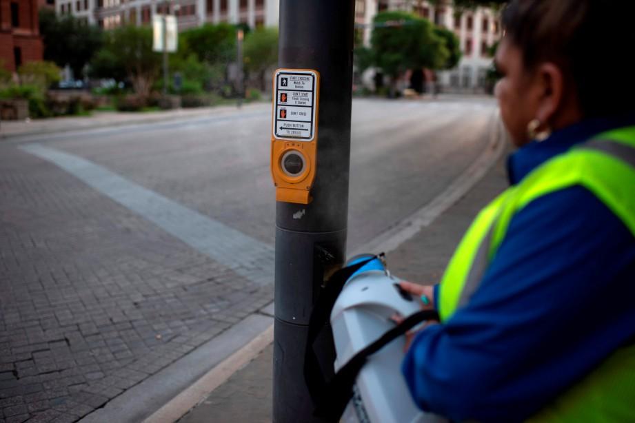 PEKERJA membersihkan butang penekan di lampu isyarat di pusat bandar San Antonio, Texas. FOTO AFP