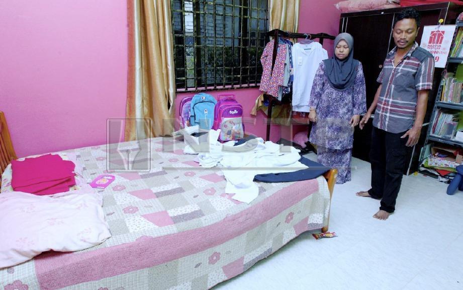 Nur Syahida dan Zawawi melihat kelengkapan sekolah anak mereka. FOTO Syamsi Suhaimi