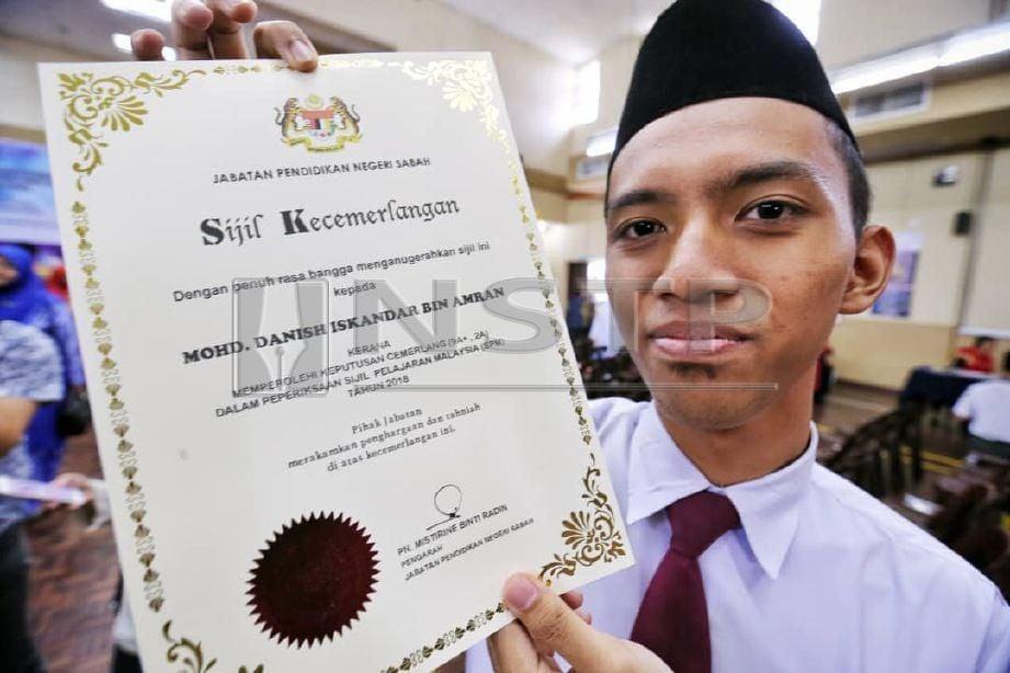 Mohd. Danish Iskandar Amran, menunjukkan sijil yang diterima apabila tersenarai pelajar cemerlang dengan keputusan 9A+, 2A ketika pengumumkan keputusan peperiksaan Sijil Pelajaran Malaysia (SPM) 2018 peringkat negeri Sabah di Dewan Sekolah Menengah Lok Yuk, Likas. FOTO Khairull Azry Bidin