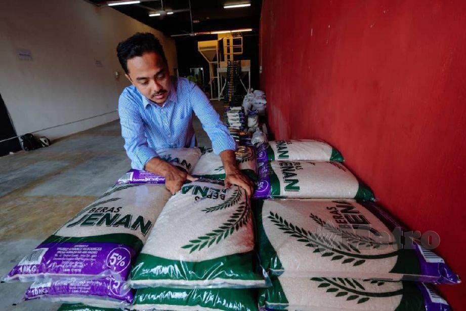 PENIAGA beras, Mohd Norazim Abd Razak,33, menyusun beras yang dijualnya di sebuah lot kedai di Jitra. FOTO Noorazura Abdul Rahman