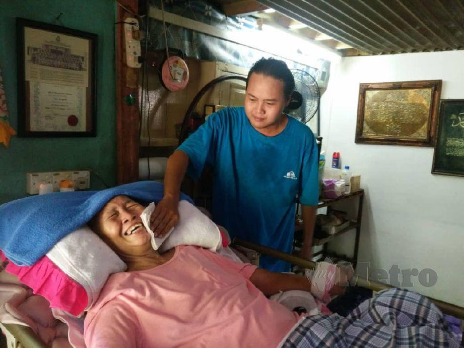 SAMAL Arizon Alias,34, mengelap peluh ibunya Samsiah Md Saad,68, yang lumpuh keseluruhan badan akibat strok sejak 2011. FOTO Noorazura Abdul Rahman
