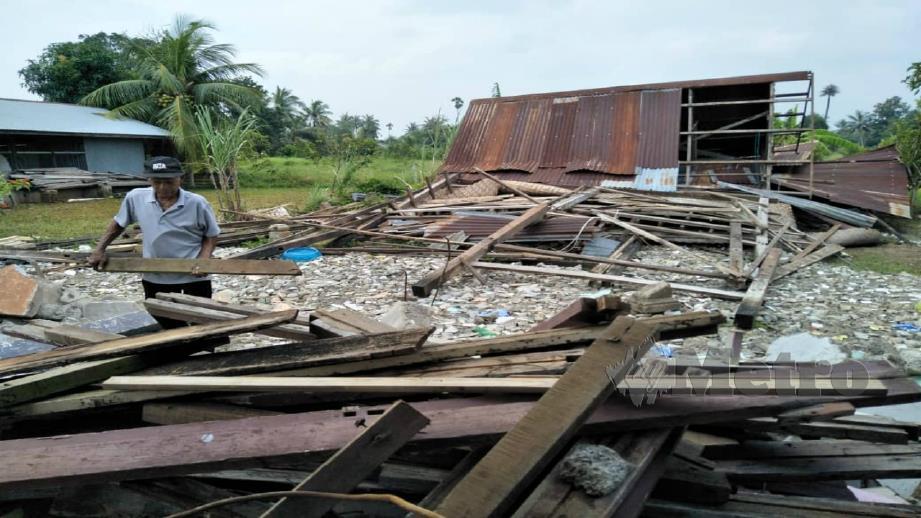 AHMAD menyusun serpihan kayu rumahnya selepas runtuh akibat dipukul ribut di Kampung Sempering. FOTO DZIYAUL AFNAN ABDUL RAHMAN