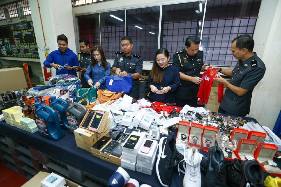 KETUA Penguatkuasa KPDNHEP Kuala Lumpur Azeem Nazuri (tengah) bersama pegawai dan anggota melupuskan barang-barang tiruan yang dirampas di stor KPDNKK Segambut. FOTO Muhd Zaaba Zakeria